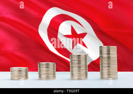 Tunisia flag waving in the background with rows of coins for finance and business concept. Saving money. - Stock Photo