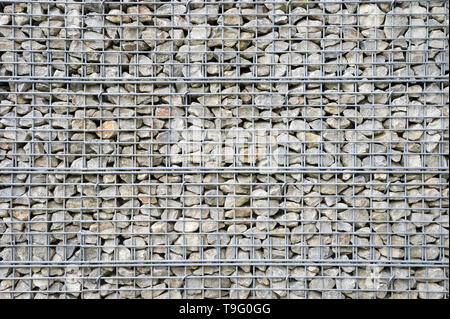 Abstract architectural background of rough retaining wall made from rocks in steel cage gabion baskets - Stock Photo