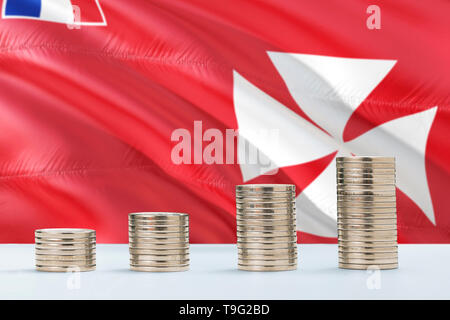Wallis And Futuna flag waving in the background with rows of coins for finance and business concept. Saving money. - Stock Photo
