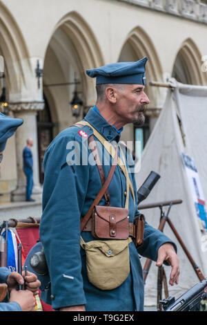 Krakow, Poland - September 23, 2018:   Tall Man dressed in Polish uniforms from World War I among tourists at krakow's main square  - Stock Photo