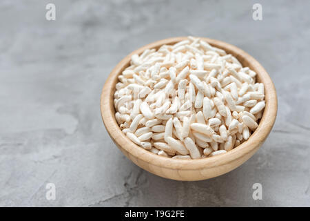Puffed rice in a wooden bowl on a gray background, concept of healthy eating vegan food. Close up, selective focus, copy space. - Stock Photo