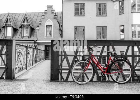 A picture of a lonely red bike standing in the typical street in Stockholm by the bridge to a house. The bike looks to be modern in a retro style. - Stock Photo