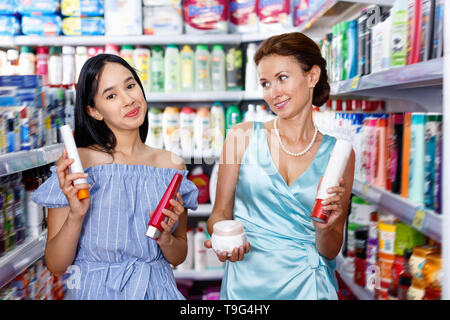 Stylish cheerful  female and girl attentively looking haircare products at shop - Stock Photo