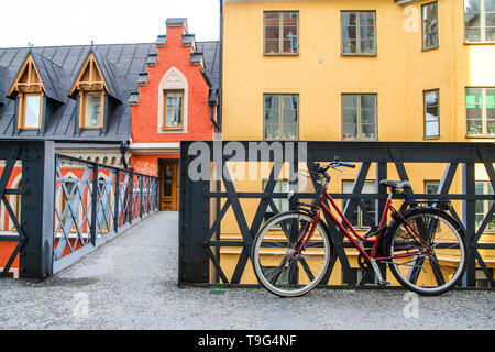 A picture of a lonely red bike standing in the typical street in Stockholm by the bridge to a house. The bike looks to be modern in a retro style - Stock Photo