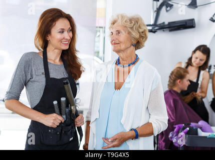 Smiling elegant senior woman posing together with skillful female stylist in modern space of barbershop - Stock Photo