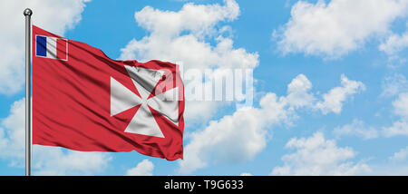 Wallis And Futuna flag waving in the wind against white cloudy blue sky. Diplomacy concept, international relations. - Stock Photo