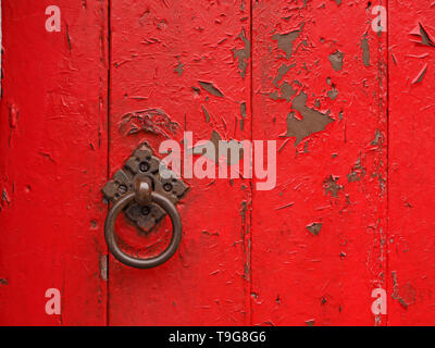 flaking red paint on old solid timber barn door with shiny cast iron ring door handle on ornate diamond pattern fixing plate in Cumbria,England UK - Stock Photo