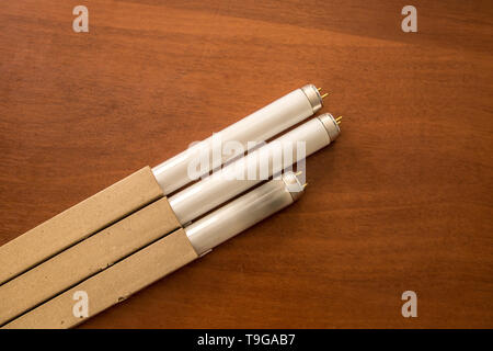 fluorescent lamps on the table, burnt and new - Stock Photo