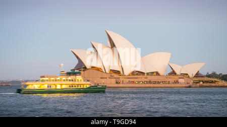 SYDNEY, AUSTRALIA - FEBRUARY 11, 2019: A ferry passing Sydney Opera House, Australia's most recognisable building, at night. - Stock Photo
