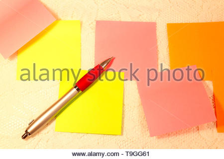 Several sticky notes in different colors and a ink pen lies on a white lace background. - Stock Photo