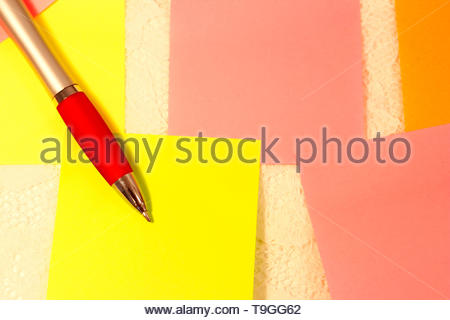 Close up on several sticky notes in different colors and an ink pen - Stock Photo
