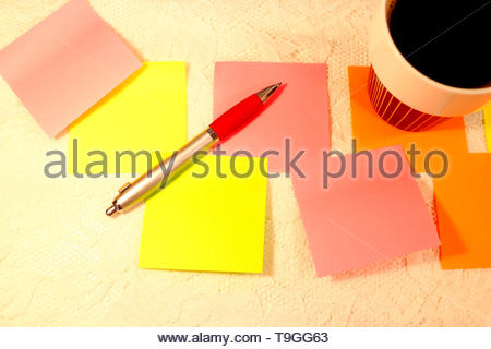 Several sticky notes in different colors lies scattered on a table. A cup of black coffee stands in the corner and an ballpoint pen lies on top of the - Stock Photo