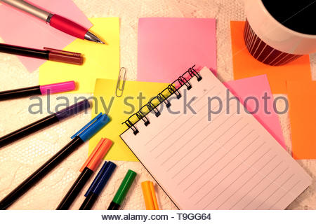 A notebook with unwritten lined pages lies among several sticky notes and felt pens in different colors. A cup of black coffee. - Stock Photo