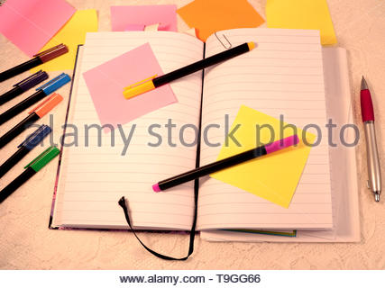 An open journal with sticky notes and two colored felt pens on top of it. Several colored pencils and sticky notes lies on the side of the book. - Stock Photo