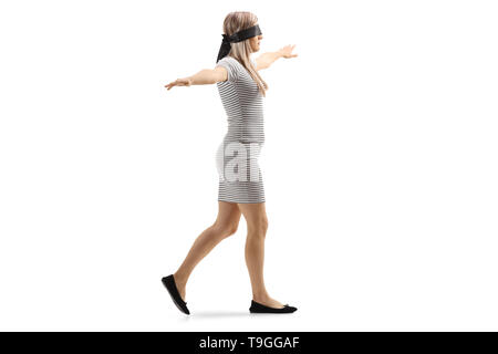 Full length profile shot of a woman wearing blindfold and walking with spread arms isolated on white background - Stock Photo