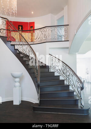 Looking up spiraling wooden staircase with wrought iron balusters onto upstairs hallway inside a luxurious residential home, Quebec, Canada. This image is property released. CUPR0350 - Stock Photo