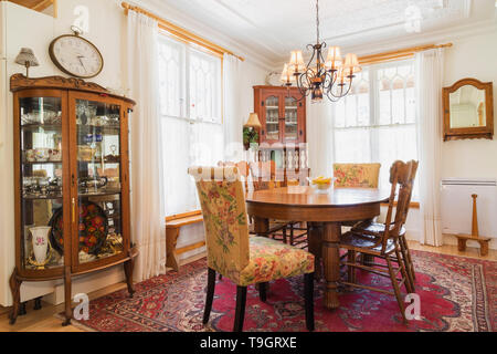 Oval oak wood dining table with press-back chairs, wood with glass doors corner buffet, crimson red rug in dining room with lit antique chandelier inside an old 1920s house, Quebec, Canada. This image is property released. CUPR0349 - Stock Photo