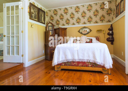 1930s double bed with pinewood headboard and white bedspread, antique burled maple pulaskis apothecary bureau, stained and oiled pinewood floorboards in guest bedroom on upstairs floor inside an old 1920s house, Quebec, Canada. This image is property released. CUPR0349 - Stock Photo