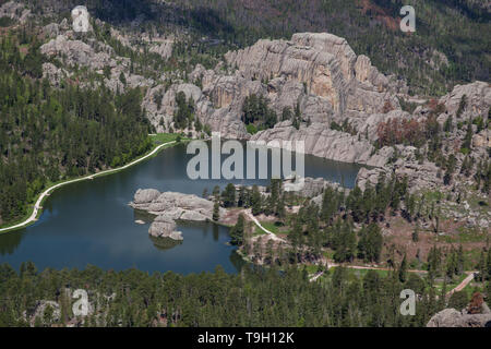 An aerial view of Sylvan Lake in South Dakota on a sunny day with large rock formations and tall trees surrounding it. - Stock Photo