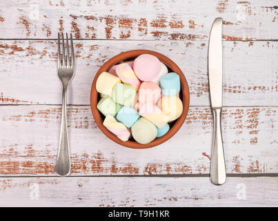 Marshmallows in a round bowl on white wooden background. Fork, knife and bowl white, wooden background. Top view. - Stock Photo