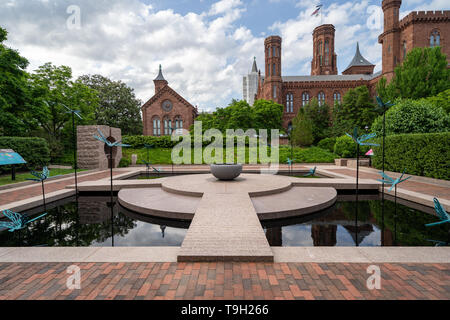 Washington, DC - May 9, 2019: The Moongate Garden with dragonfly statues in the Enid Haupt Garden and the Smithsonian Castle on the National Mall - Stock Photo