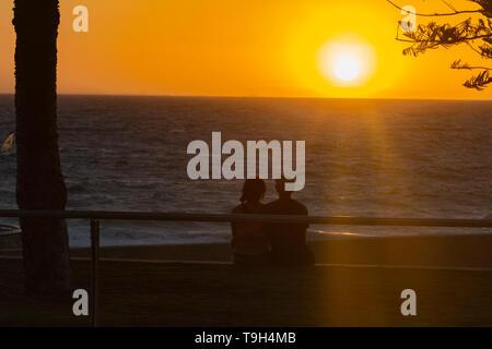 Nice Scene sunset and a couple watching the horizon in the beach, Perth, Australia. - Stock Photo
