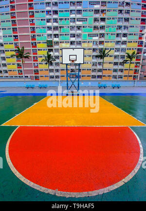 The bright colours of the basketball court and apartments of the Choi Hung estate in Hong Kong - Stock Photo