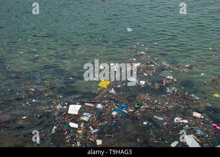 Human trash floating on the sea at Stanley Bay in Hong Kong - Stock Photo