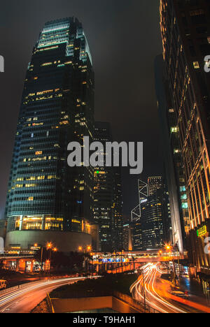 Skyscrapers and light trails in downtown Hong Kong - Stock Photo