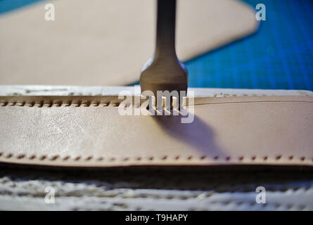 Leather working four prong chisel hole punch close up. Punching holes for stiching with metal tool. Selective focus. - Stock Photo