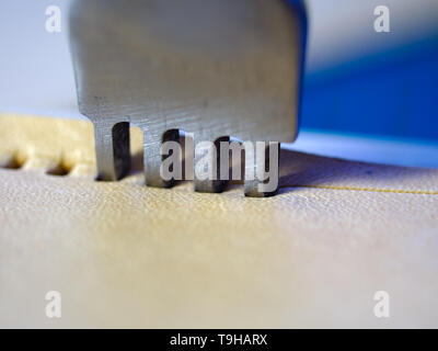 Leather working four prong chisel hole punch close up macro. Punching holes for stiching with metal tool. Selective focus. - Stock Photo