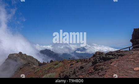 Hiking on mountain ridge with heavenly clouds on rocky mountain peak in La Palma island, Spain, at Rogue Muchachos - Stock Photo