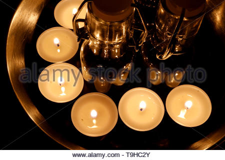 Several tiny candles standing on metallic surface, burning in the dark. Tiny glass bottles in the middle of the candles. - Stock Photo