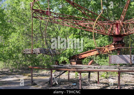 Abandoned carousel in the amusement park near the ghost town of Pripyat, Chernobyl exclusion zone, Ukraine - Stock Photo