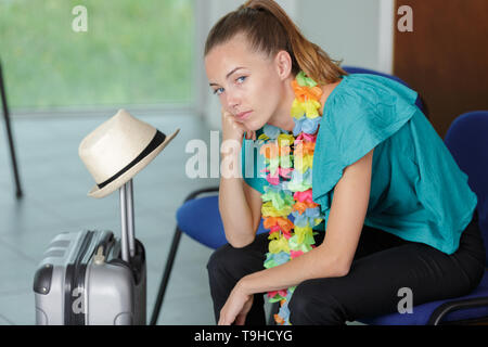 woman sitting in an airport lounge with her luggage - Stock Photo