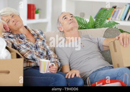 senior couple sleeping in front of stacked moving boxes - Stock Photo