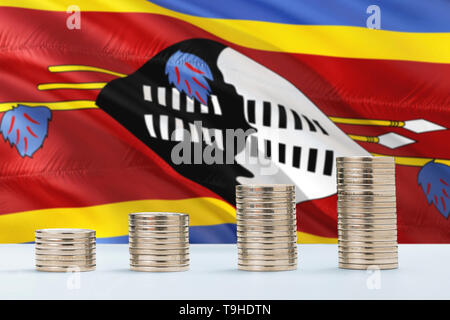 Swaziland flag waving in the background with rows of coins for finance and business concept. Saving money. - Stock Photo