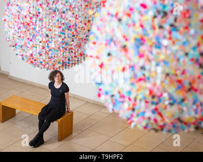 A visitor views 'As I Live and Breathe' - an installation composed of thousands of fragments of colourful waste polythene torn by hand from used shopping bags by artist Claire Morgan - at the Horniman Museum and Gardens, London, part of a series of specially commissioned works drawing on the theme of waste and the impact that humans have on their surroundings. - Stock Photo