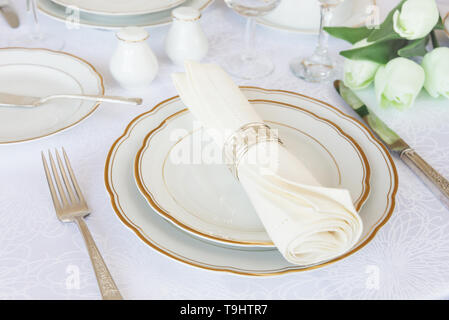 Classic serving for a gala dinner with luxurious porcelain, silverware and tulip flowers on a white tablecloth - Stock Photo
