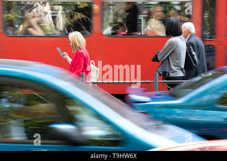 Belgrade, Serbia -  April 22, 2019: People waiting at bus stop on busy city street on a sunny spring day with passing red tram and cars in motion blur - Stock Photo