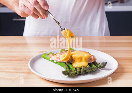 Man's hands pouring hollandaise sauce on top of delicious baked salmon with steamed green asparagus. Food presentation preparation process - Stock Photo