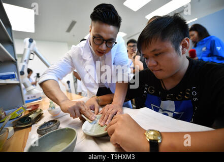 Hainan, China. 18th May, 2019. A restorer of ancient ceramics guides the audience to polish the ceramics at the China (Hainan) Museum of the South China Sea in Qionghai, south China, on May 18, 2019. The museum invited the audience to visit and experience the restoration of ancient ceramics on the International Museum Day. Credit: Guo Cheng/Xinhua/Alamy Live News - Stock Photo