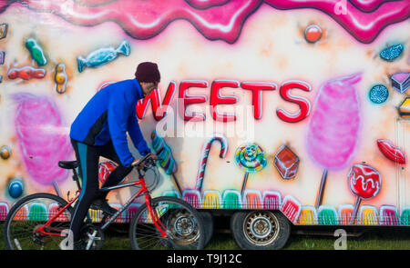 Seaton Carew, County Durham, UK. 19th May 2019. UK weather: a cyclist rides past a funfair sweet stall on a glorious Sunday morning at Seaton Carew on the north east coast of England. Credit: Alan Dawson/Alamy Live News - Stock Photo