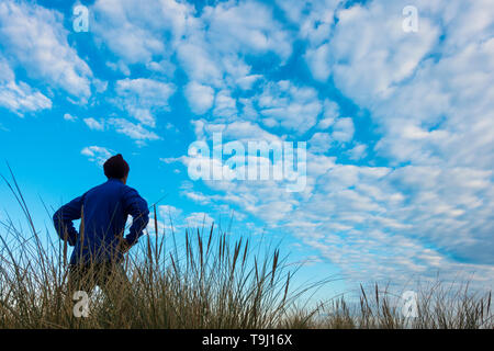 Seaton Carew, County Durham, UK. 19th May 2019. UK weather: a jogger looks out over the dunes as early morning sun burns off a thin layer of cloud on a glorious Sunday morning at Seaton Carew on the north east coast of England. Credit: Alan Dawson/Alamy Live News - Stock Photo