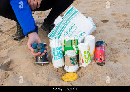 Seaton Carew, County Durham, UK. 19th May 2019. UK weather: a glorious morning for Plogging. A jogger collects rubbish on his morning run through the dunes at Seaton Carew on the north east coast of England. Plogging (picking up litter while jogging) is a Scandinavian lifestyle trend where joggers pick up rubbish/plastic as they run.Also found on the beach were Taprogge Balls (in jogger's hand), used to clean cooling pipes in power stations. Taprogge balls previously found on this stretch of coast were found to have come from the nearby Hartlepool nuclear power station (they are said to be har - Stock Photo