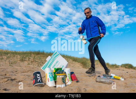 Seaton Carew, County Durham, UK. 19th May 2019. UK weather: a glorious morning for Plogging. A jogger collects rubbish on his morning run through the dunes at Seaton Carew on the north east coast of England. Plogging (picking up litter while jogging) is a Scandinavian lifestyle trend where joggers pick up rubbish/plastic as they run. Credit: Alan Dawson/Alamy Live News - Stock Photo