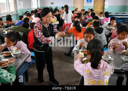 (190519) -- WANRONG, May 19, 2019 (Xinhua) -- Teacher Sun Yinli takes photos of pupils having lunch at Dingfan Primary School in Gaocun Township of Wanrong County, north China's Shanxi Province, May 15, 2019. Most of the 110 pupils at Dingfan Primary School are left-behind children, whose parents have become migrant workers in towns or cities. Some of the students came from registered poor families in Dingfan and nearby villages. In September of 2015, school master Zhao Yingjie applied to add the school onto the list of Free Lunch for Children (FLC), the public initiative to offer free meals t - Stock Photo