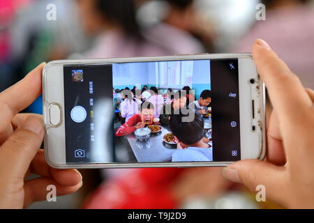 (190519) -- WANRONG, May 19, 2019 (Xinhua) -- A teacher of the Dingfan Primary School takes photos of pupils having lunch at Dingfan Primary School in Gaocun Township of Wanrong County, north China's Shanxi Province, May 15, 2019. Most of the 110 pupils at Dingfan Primary School are left-behind children, whose parents have become migrant workers in towns or cities. Some of the students came from registered poor families in Dingfan and nearby villages. In September of 2015, school master Zhao Yingjie applied to add the school onto the list of Free Lunch for Children (FLC), the public initiative - Stock Photo