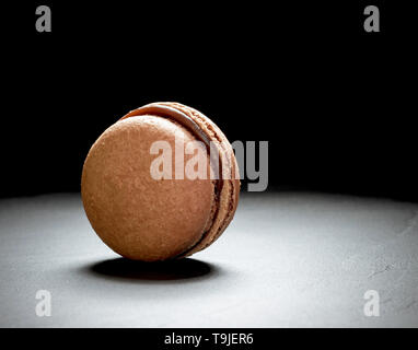 Chocolate macaron at the black background, close up - Stock Photo