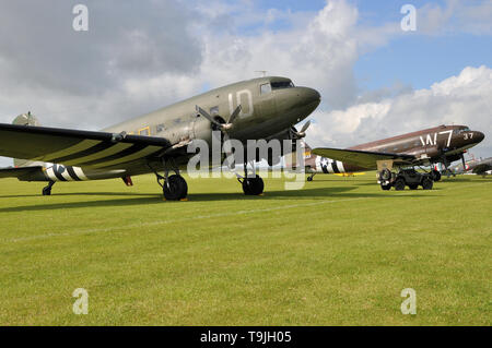 Douglas C-47 Skytrain planes in period camouflage markings - including D Day 'invasion stripes'. Second World War transport plane with Jeep - Stock Photo
